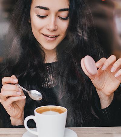 Porträtaufnahme einer Frau, die einen Cookie hält und Kaffee trinkt