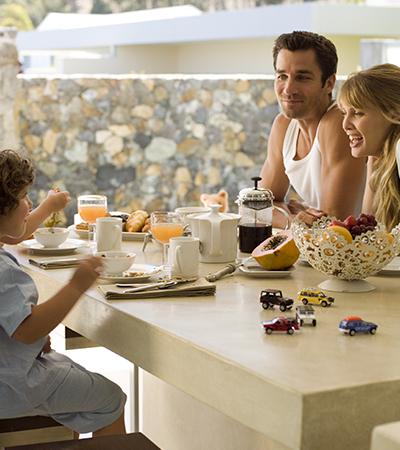 Familie mit zwei Kindern beim Brunchen am Frühstückstisch