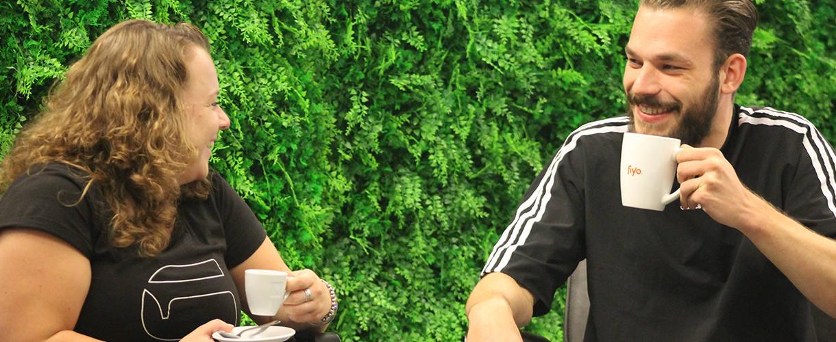 Eine Frau und ein Mann trinken lachend Kaffee