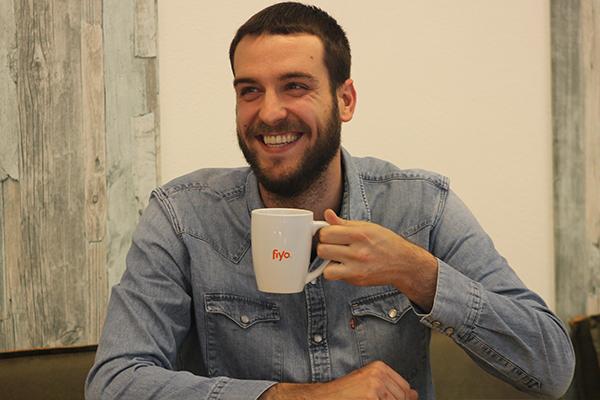 Junger Mann aus Spanien trinkt lachend Kaffee