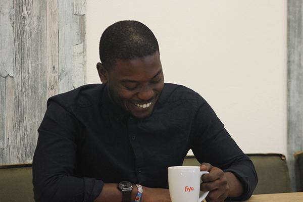 Junger Mann aus Frankreich sitzt lachend am Tisch, Kaffeebecher in der Hand
