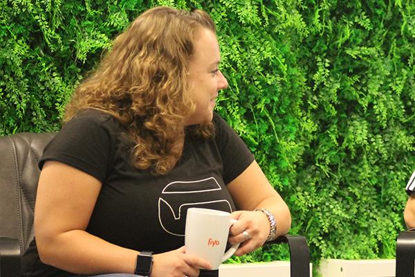 Junge Frau aus den Niederlanden sitzt vor grünem Hintergrund mit Kaffeebecher in der Hand