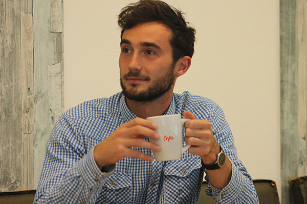 Junger Mann aus Polen mit Kaffeebecher in der Hand guckt in die Ferne